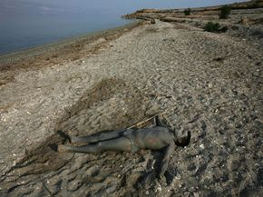 An Israeli hiker covered in Dead Sea mud basks in the sunlight. The Dead Sea's mud has proven therapeutic qualities.