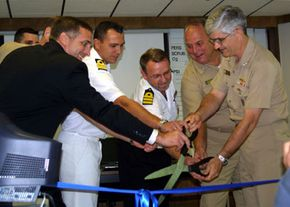 Admiral Kirkland H. Donald, right, and members of the International Submarine Escape and Rescue Liaison Office cut the ribbon at the opening of the new ISMERLO Coordination Center, located in Norfolk, Va.