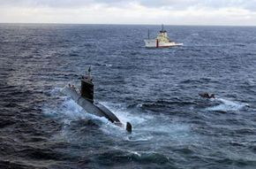 Stricken Canadian submarine HMCS Chicoutimi wallows in heavy seas as a salvage vessel moves into position.