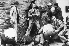 Agents tend to presidential secretary James Brady after he was shot by John Hinckley Jr.  during an assassination attempt on Pres. Ronald Reagan.