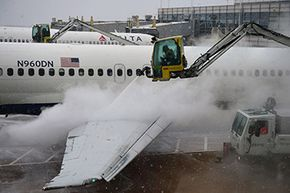 Workers deice a Delta Airlines plane at Ronald Reagan Washington National Airport in March 2015.