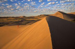 A hiker climbs a sand dune in Bruneau Sand Dunes State Park, Idaho