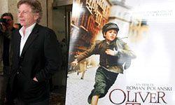 """Roman Polanski poses next to the poster for his 2005 """"Oliver Twist"""" film."""