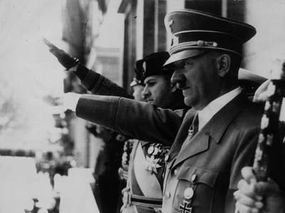 circa 1944: Adolf Hitler gives the fascist salute at a parade. Visible on the balcony with him are Galeazzo Ciano and Italian Benito Mussolini (far left). Just visible on the right is the hand Hermann Goering holding his Field Marshal's baton.