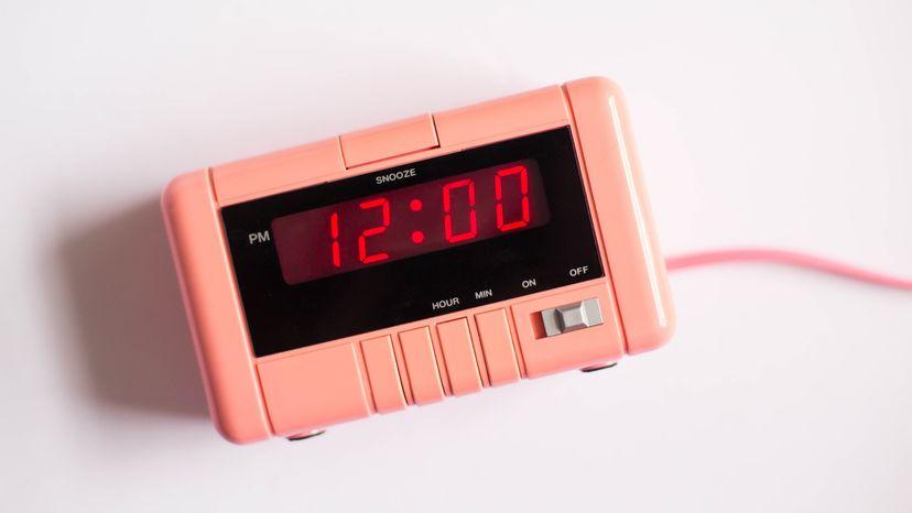 Pink alarm clock on white background displaying 12 PM