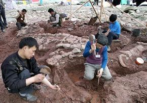 Chinese scientists excavate a dinosaur fossil discovered at a site on the shore of the Jialing river near southwestern Chongqing municipality in 2004.