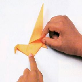 Folding its legs will help your origami dinosaur stand.