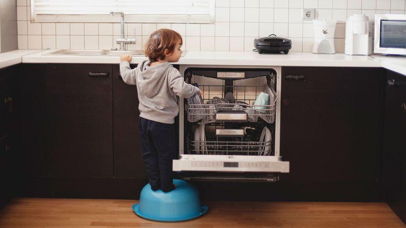child stacking dishwasher