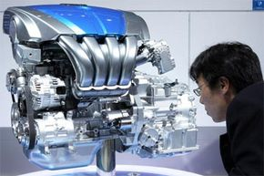 """A visitor examines the new Mazda Motor Corp.'s direct injection engine """"Mazda SKY-G"""" during the Tokyo Motor Show in October 2009."""