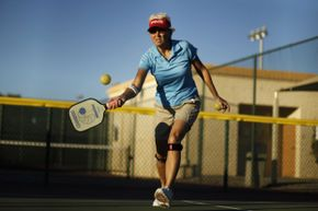 Pickleball is played with a paddle and a ball similar to the ones used for whiffleball. No actual pickles are involved.
