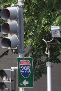 A camera is placed near a traffic light for drivers who run red lights on Constitution Avenue in Washington, DC. The camera will take a picture of the car and license plate and the offender will be mailed a citation.