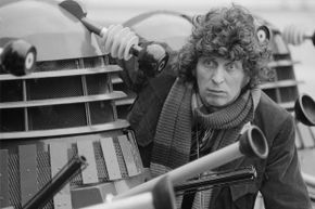 """Actor Tom Baker, as the Doctor from the BBC science fiction TV series """"Doctor Who,"""" poses with the Doctor's arch enemies, the Daleks, in 1975."""
