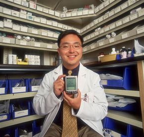 Peter Hahn, resident at Cornell Medical Center proudly displaying the Palm Pilot he uses as a drug database.
