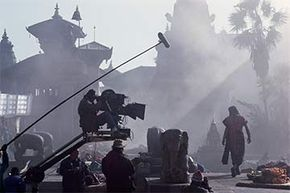The dolly grip is the person pushing the wheeled contraption where the camera sits (seen here on the 'Little Buddha' set).