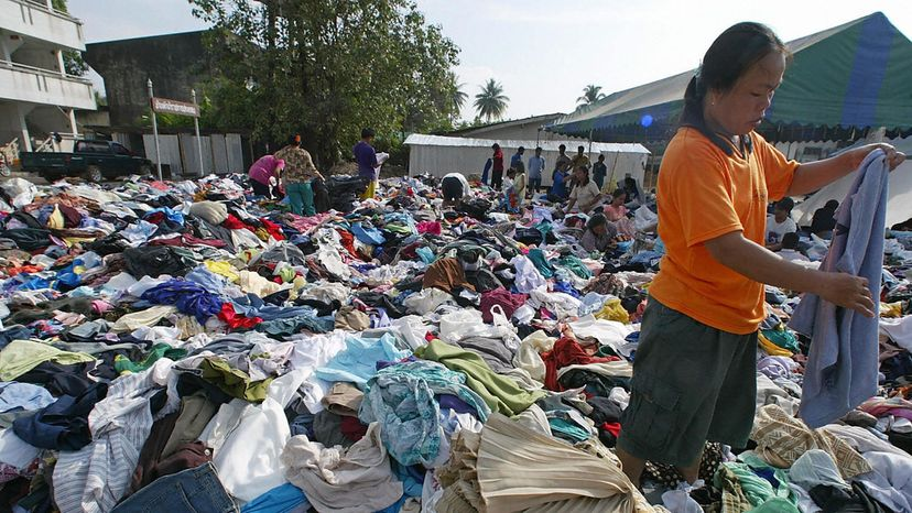 woman looking at clothes donations, Thailand