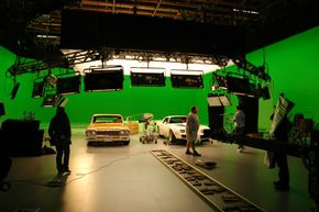"""The cast and crew set up for a shot in front of the green screen on the set of """"Drive"""""""