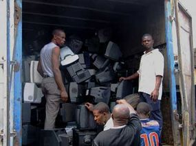 Workers in Lagos, Nigeria, unload imported TVs and PC monitors, most of which will be sent to the local dumps. From there, they will be scavenged for recycling and then burned. 