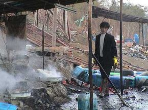 A man in Guiyu, China, heats a combination of nitric and hydrochloric acid, while inhaling acid fumes, chlorine and sulfur dioxide, without respiratory protection. Leftover acids and sludge are dumped in the river.