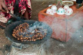 The hostess of an Ethiopian coffee ceremony roasts the coffee beans, creating aromatic smoke.