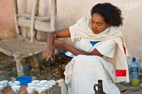 A coffee ceremony hostess in Axum, Ethiopia pours a round of coffee.