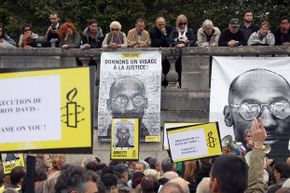 Protestors hold placards of rights group Amnesty International during a demonstration in Paris, in support of Troy Davis (featured on the posters).