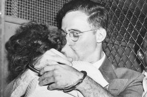 Bound for separate cells, handcuffed Julius Rosenberg and his wife, Ethel, share a fervent kiss in a prison van outside Federal court after arraignment on atomic spy charges in 1950.