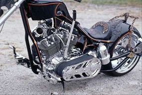 Seat and rear fender are set off by intricate leatherwork, a pistol-grip hand shifter picks the gears, and a chrome bottle stores fuel for the flamethrower.