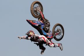 Spanish rider Dany Tores does the lazy boy trick on his motorcycle.