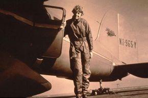 Amelia Earhart beside her beloved Lockheed Electra airplane.