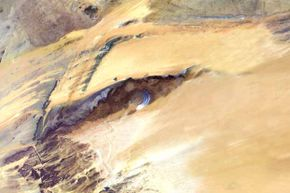 This satellite image shows the Richat Structure. Although it resembles an impact crater, the Richat Structure formed when a volcanic dome hardened and gradually eroded, exposing the onion-like layers of rock.