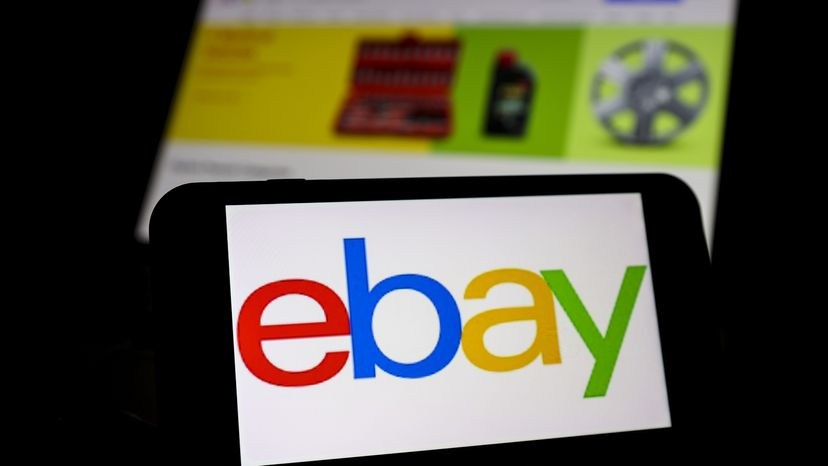 The logo of eBay is displayed on a smartphone and the website of eBay is displayed on a screen behind it