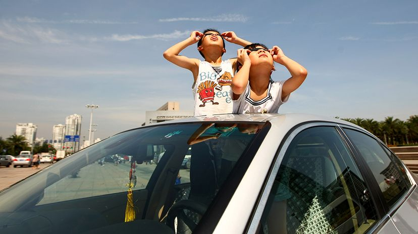 Two children observe a total solar eclipse from the sunroof of a car on July 22, 2009, in Wenzhou, China. The longest total eclipse of the sun of this century triggered tourist fever across Asia, straining infrastructure. China Photos/Getty Images