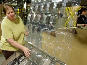 A quality control employee checks containers made from corn plastic as they come out of the forming machine.
