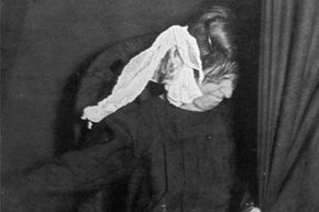 A strange visage appears on a piece of cloth next to the head of medium Marthe Beraud (aka Eva C) during a seance, circa 1910. Ectoplasm got its start in such seances.