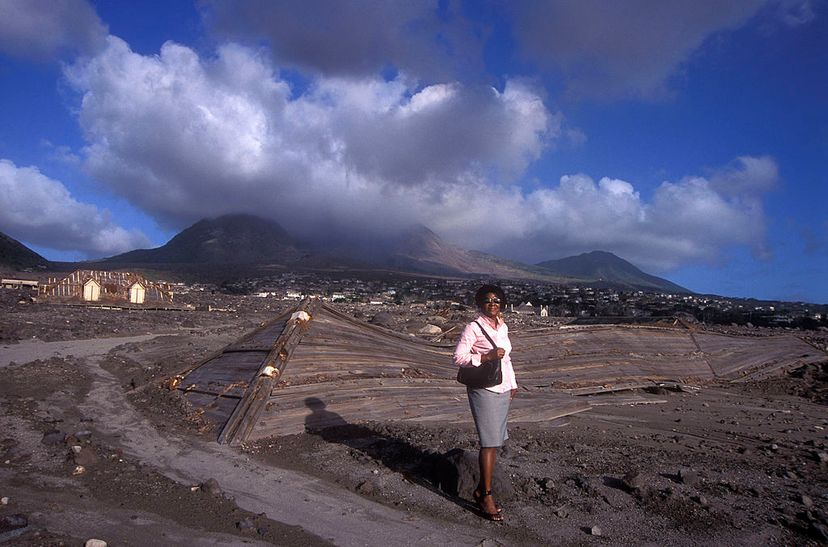 Helena Codrington stands where Montserrat's Treasury building once stood and where she used to work before the Soufriere-Hills volcano erupted. Since this photo was taken in 2005, it's likely that the tops of this building are now covered with ash. Christopher Pillitz/Exclusive by Getty Images)