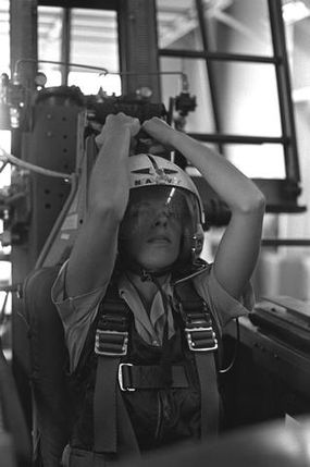 A pilot prepares to pull down the face curtain that will launch the ejection seat up the track of the ejection-seat trainer.