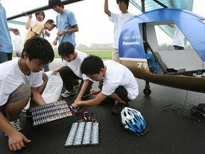 The pilot of the Oxyride Dry Cell Manned Aircraft checks 160 Oxyride batteries prior to the plane's first flight at the Honda Airport on July 16, 2006 in Saitama, Japan. The vehicle was the first manned aircraft powered exclusively by 160 AA batteries.