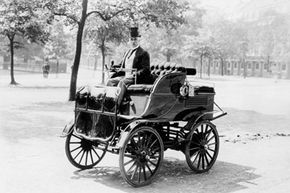 How old are electric cars? Much older than you might think. Here's Roger Wallace perched atop his electric car in 1899.
