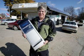 Mike Howard holds an electric-car charger outside his service station in Elk Horn, Iowa. Elk Horn has four of the devices ready to power up any electric vehicles that venture through western Iowa.