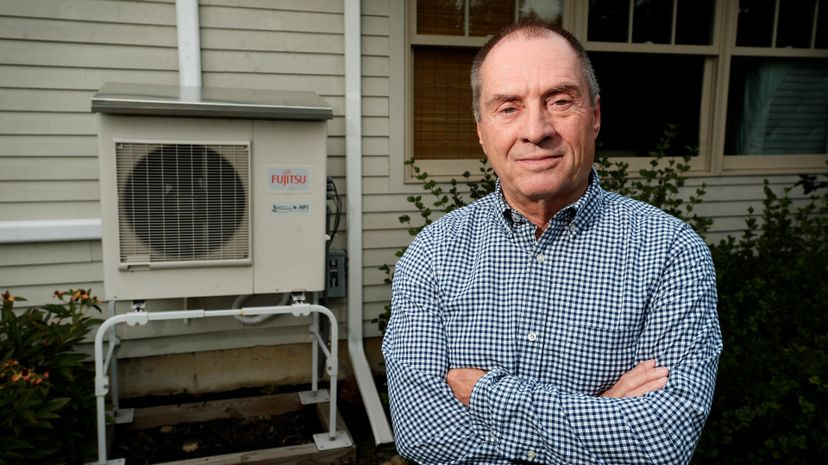 Man poses with heat pump