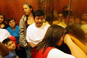A woman tries to breathe fresh air through a crack in the doors when homeowners and Association of Community Organizations for Reform Now (ACORN) activists became stuck in a California elevator on March 25, 2009.