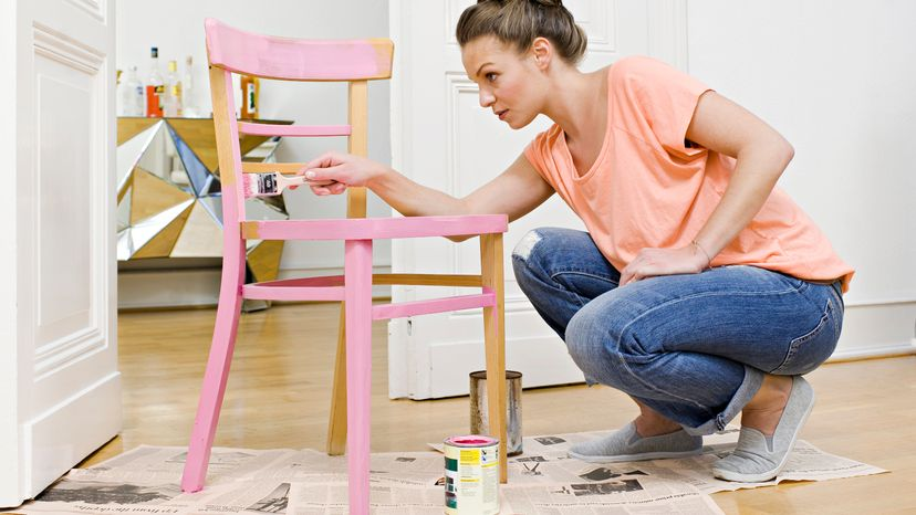 Woman Painting Furniture with Pink Enamel Paint