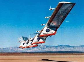 NASA's solar-electric, high-altitude flying wing, the Helios, lands at Edwards Air Force Base, California, after a test flight. The 247-foot-wingspan, 1,640-pound aircraft is designed to fly at high altitudes (100,000 feet) for sustained periods.