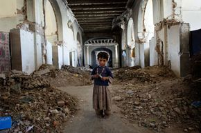 An Afghan girl stands amid the decimated Darul Aman Palace outside Kabul, Afghanistan, on Oct. 21, 2010.