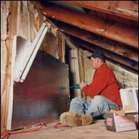 A worker installs insulation in a demonstration during Energy Star's home-sealing initiative.