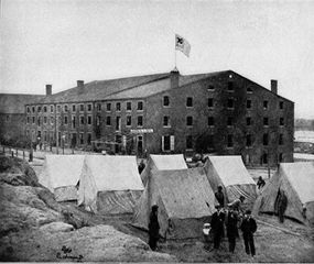 Soldiers, other people, and tents of Confederates outside of Libby Prison, Richmond, Virginia in 1863.