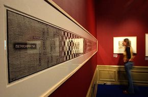 """A visitor admired M.C. Escher's """"Metamorphosis III"""" at The Hague's """"Escher in the Palace"""" exhibit in 2003."""