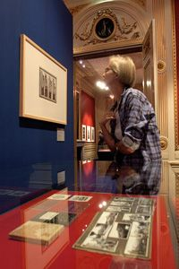 """A visitor tries to get a closer look at an Escher lithograph at The Hague's """"Escher in the Palace"""" exhibit."""