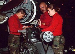 Technicians work on an M61 Vulcan Cannon.
