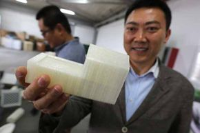 The inventor of the 3D-printed house, Ma Yihe, shows a model in Shanghai, China, 2014. See home construction pictures.